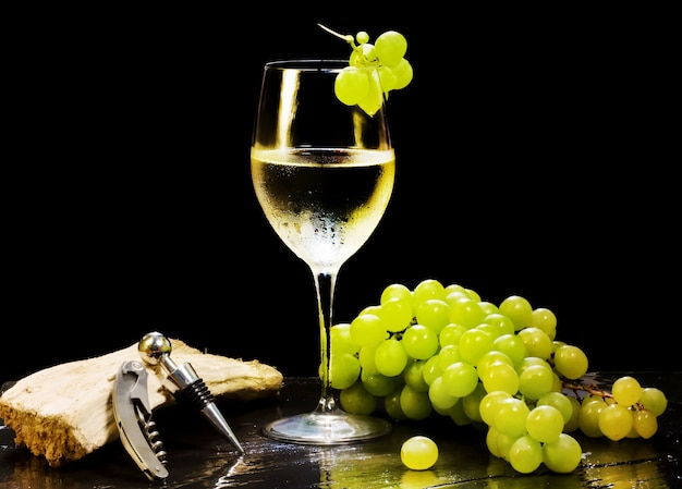 Wine glass with grapes bunch and corkscrew