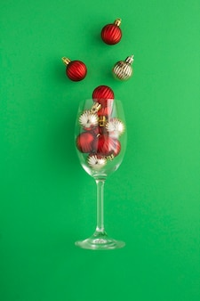 Wine glass with red and gold  balls on the green  background. close-up. location vertical.