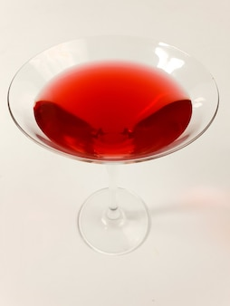Бокал с красным мартини на белом фоне