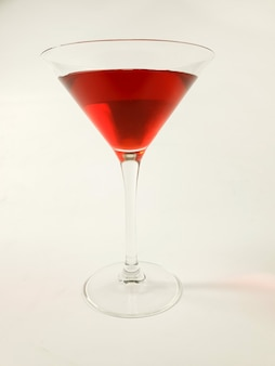 Wine glass with red martini on white background