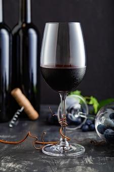 赤ワインとワイングラス。赤ワインのボトル、暗い素朴なコンクリートの背景に葉とブドウの木とブドウの房。黒い石のテーブルの上のワインの構成。