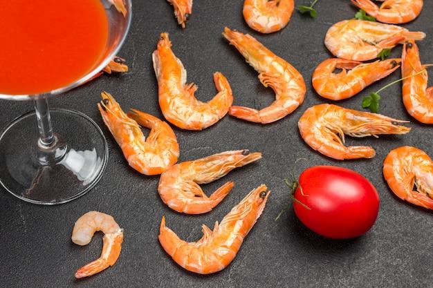 Бокал с томатным соком, красным помидором и апельсиновыми креветками на черном