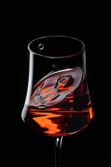 Wine glass with wine and flying drop
