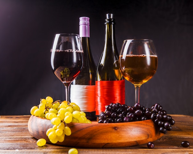 Wine glass with wine, grapes black, green on wooden tray on table
