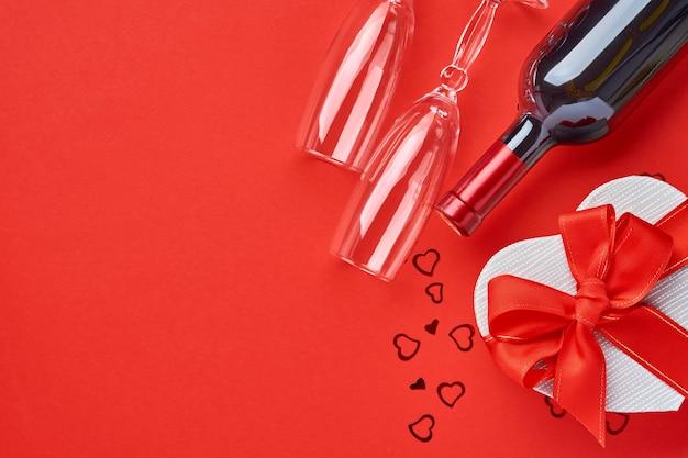 Вино, бокалы и подарочная коробка в форме сердца с красной лентой на красном фоне. открытка концепции дня святого валентина. вид сверху.