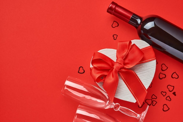 Вино, бокалы и подарочная коробка в форме сердца с красной лентой на красном фоне. открытка концепции дня святого валентина.