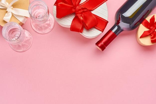 Вино, бокалы и подарочная коробка в форме сердца с красной лентой на розовом фоне. открытка концепции дня святого валентина. вид сверху.