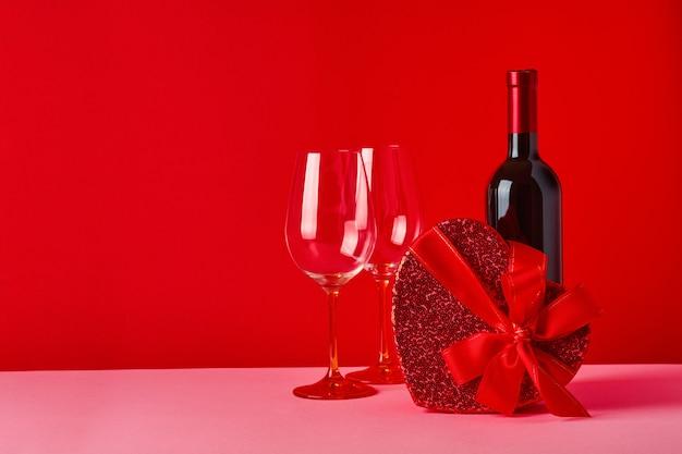 緋色のテーブルに赤いリボンが付いたハートの形のワイン、グラス、ギフトボックス。バレンタインデーのコンセプトセレクティブフォーカス。