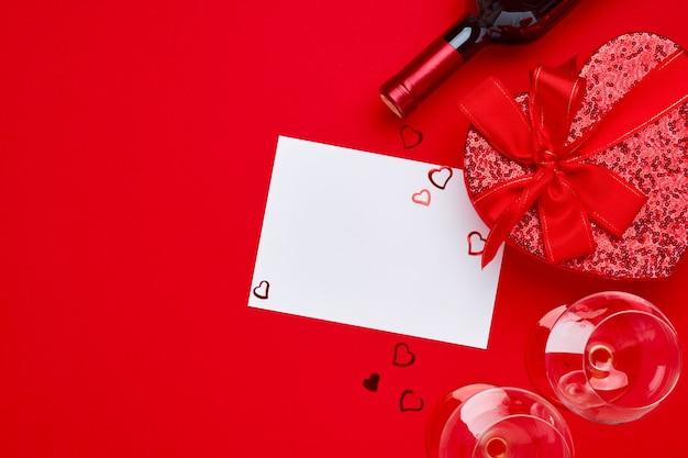緋色のテーブルに赤いリボンが付いたハートの形のワイン、グラス、ギフトボックス。バレンタインデーのコンセプト上面図。コピースペースのある平面図フラットレイ。