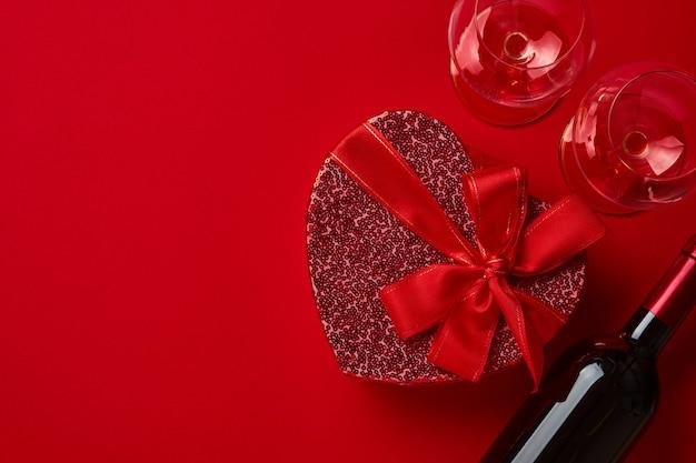 緋色のテーブルに赤いリボンが付いたハートの形のワイン、グラス、ギフトボックス。バレンタインデーのコンセプト上面図。