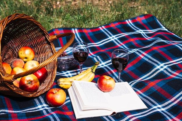 Wine glasses; apple; banana and book on blanket