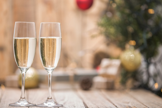 Wine glasses in front of a christmas tree