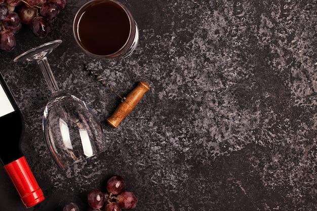 暗い背景の上のワイングラス、ブドウ、コルク栓抜き