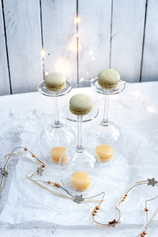 Wine glasses and pastel macaroons cookies on white background