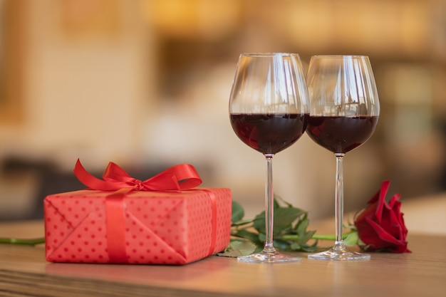 Wine glasses, present and roses on the wooden table in front of beige warm background. love and holiday concept