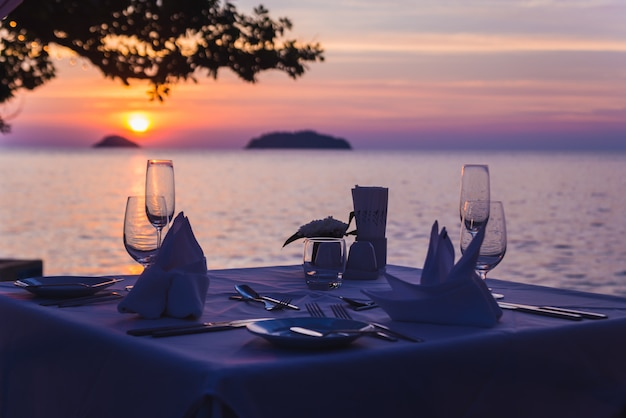 Wine glasses on the table of bar. sunset over the sea