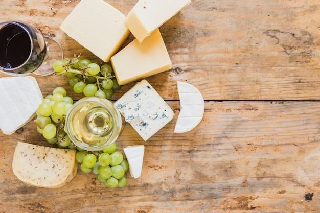 Wine glasses with grapes and variety of cheese blocks on wooden desk