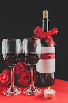 バラや背後のボトルとワイングラス