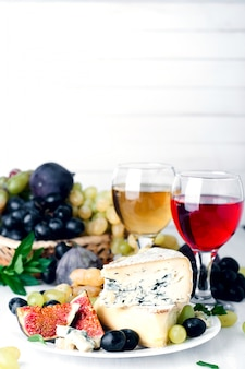 Wine, grape and cheese over white