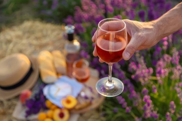 グラスワインは、ラベンダー畑で女性と男性が持っています。セレクティブフォーカス。自然。