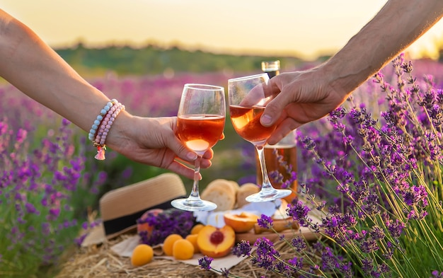 Вино в бокалах держат женщина и мужчина в лавандовом поле. выборочный фокус. природа.
