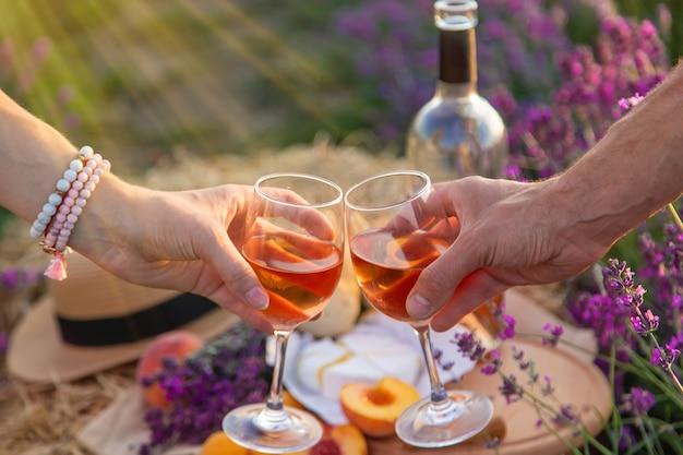 グラスワインは、ラベンダー畑で女性と男性が持っています。セレクティブフォーカス。