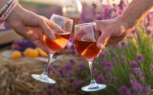 Вино в бокалах держат женщина и мужчина в лавандовом поле. выборочный фокус.