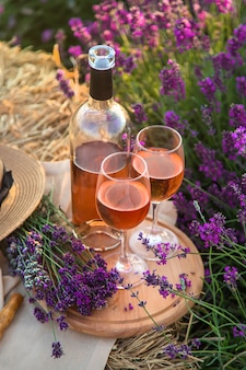 グラスワイン。ラベンダー畑でのピクニック。セレクティブフォーカス。自然。