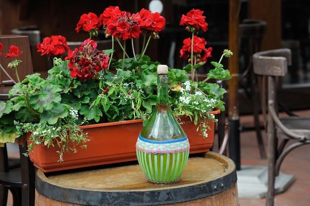 꽃으로 장식된 배럴에 오래된 병의 와인