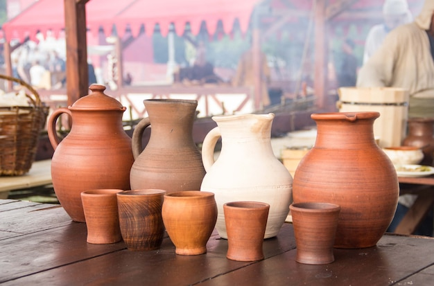 A wine jug and set of clay cups on the wooden table.