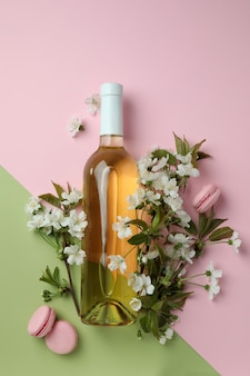 Wine, macaroons and flowers on two tone background