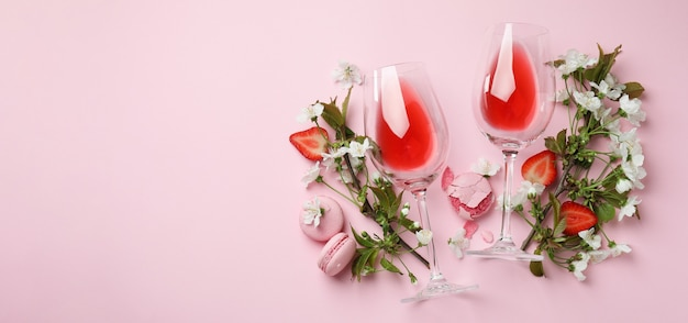Вино, миндальное печенье, клубника и цветы на розовом фоне