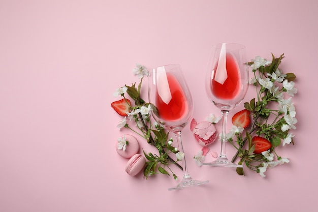Wine, macaroons, strawberry and flowers on pink background