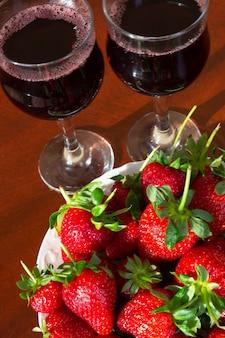 ベリーから作られたワイン。新鮮な熟したイチゴと背景の赤ワインのグラス。夏のアルコール飲料