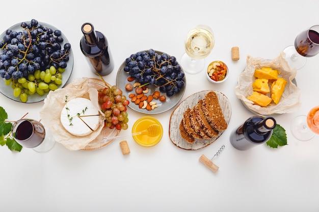 セットチーズグレープハニーナッツとワインパーティーイベントディナーテーブル。白い背景に赤ワインと地中海料理の前菜スナックを添えたお祝いのテーブル。フラットレイバナー。