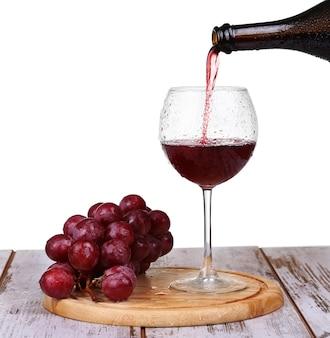 Вино наливается в бокал с виноградом и изолированными бутылками