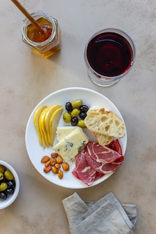 Wine snack. prosciutto, parma ham, almonds, olives, baguette, blue cheese. antipasti.