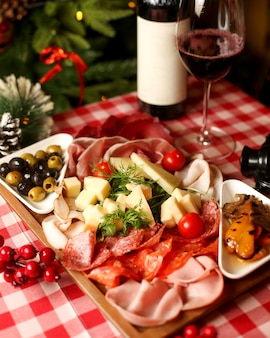 Wine snacks platter with sausages salami smoked meat slices cheese and olive