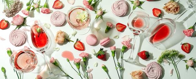 Вино, сладкая еда и цветы на белом столе