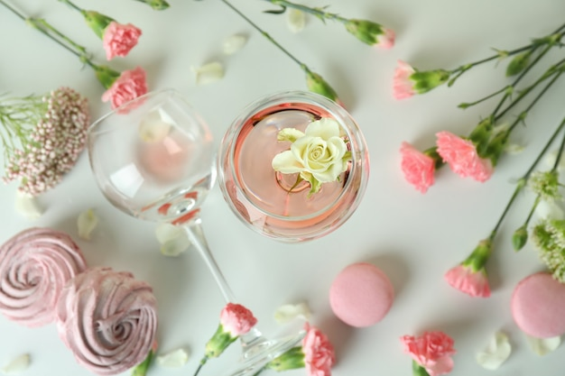 Wine, sweet food and flowers on white table