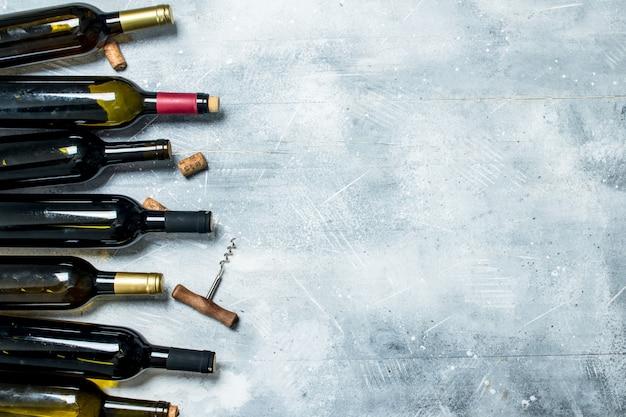 ワインテーブル。赤と白ワインのボトル。素朴なテーブルの上。