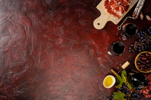 Wine and tapas on red background, top view