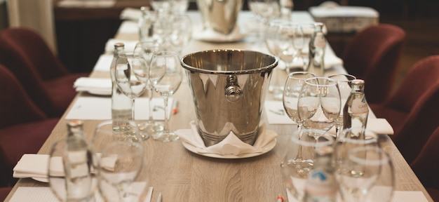 Wine tasting: table served with tasting lists, glasses, bottles with water and spittoon.