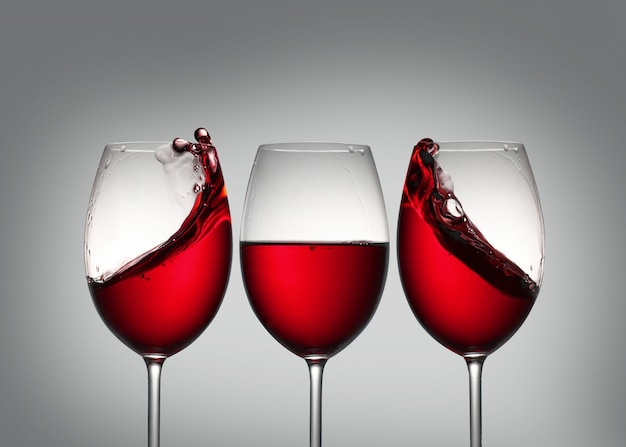 Wine . three glasses of red wine with splash in side glasses which forms symmetry.