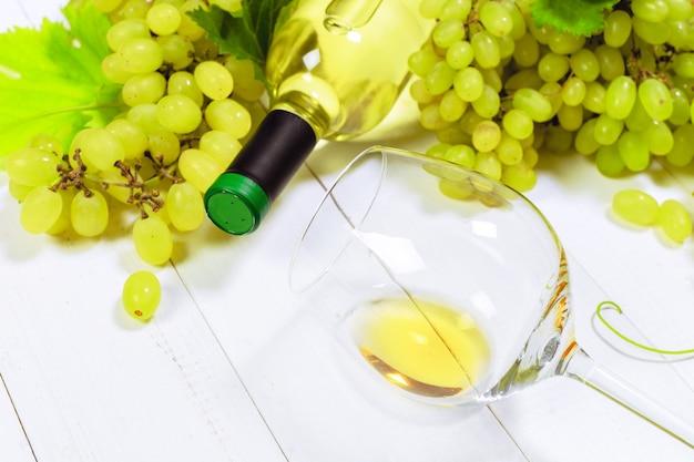 흰 포도의 가지와 와인. 나무 테이블에.