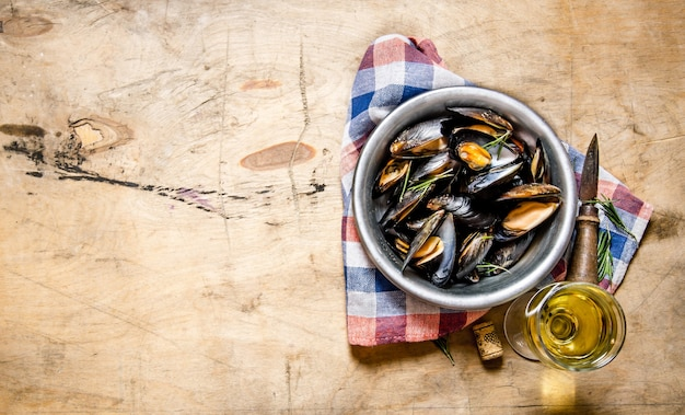Wine with clams in a cup on the fabric. on a wooden table.  free space for text . top view