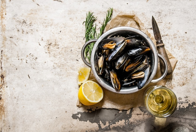 Wine with fresh clams, lemon and rosemary. on rustic background. top view