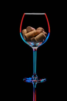 Wineglass in bright illumination, filled with corks inside isolated on a black background