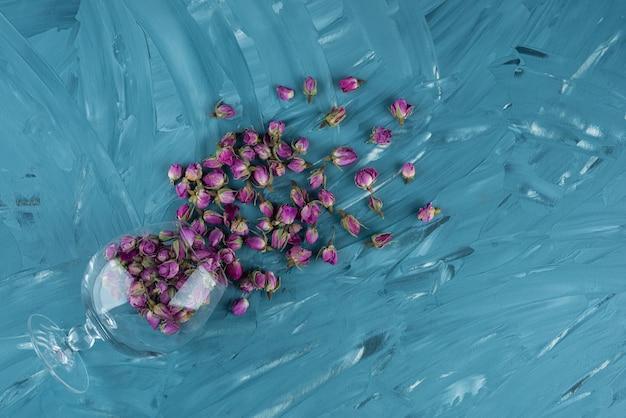 블루 테이블에 누워 말린 된 장미 꽃 봉 오리의 전체 와인 글라스.