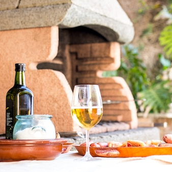 Wineglass and grilled food served on an outdoor table